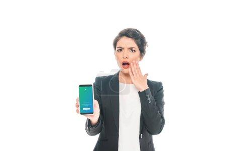 Photo pour KYIV, UKRAINE - 24 AVRIL 2019 : Femme d'affaires mixte choquée tenant un smartphone avec application Twitter à l'écran isolé sur blanc . - image libre de droit