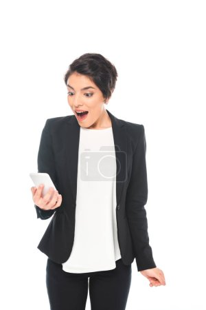Photo for Excited mixed race businesswoman in black formal wear looking at smartphone isolated on white - Royalty Free Image
