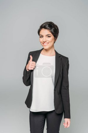 Foto de Happy mixed race businesswoman showing thumb up and smiling at camera isolated on grey - Imagen libre de derechos