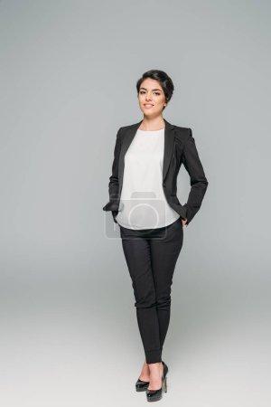 Photo pour Femme d'affaires mélangée de sourire de course retenant des mains dans des poches et regardant l'appareil-photo sur le fond gris - image libre de droit