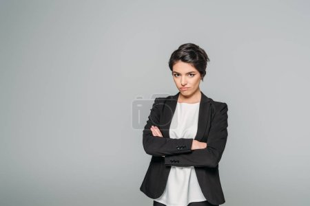 Photo for Offended mixed race businesswoman standing with crossed arms and looking at camera isolated on grey - Royalty Free Image