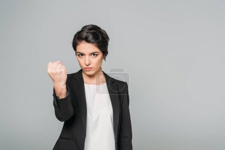 Foto de Angry mixed race businesswoman looking at camera and showing fist isolated on grey - Imagen libre de derechos