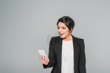 Foto de Surprised mixed race businesswoman looking at smartphone isolated on grey - Imagen libre de derechos