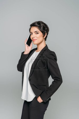 Photo for Attractive mixed race businesswoman talking in smartphone while holding hand in pocket isolated on grey - Royalty Free Image