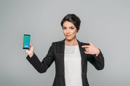 Photo pour Kiev, Ukraine - 24 avril 2019: Smiling mixed race businesswoman pointing with finger at smartphone with Twitter app on screen isolated on grey. - image libre de droit