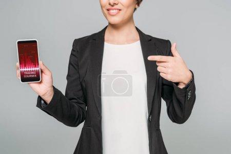 Photo pour Vue partielle de femme d'affaires mélangée de sourire de course pointant avec le doigt au smartphone avec l'application de cours de négociation sur l'écran d'isolement sur le gris - image libre de droit