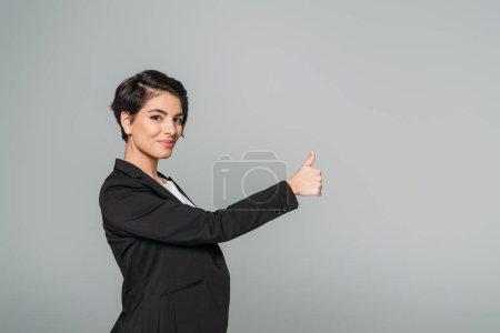 Photo pour Souriant mixte femme d'affaires montrant pouce vers le haut et regardant la caméra isolée sur gris - image libre de droit