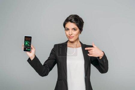 Photo pour Femme d'affaires mixte attrayante pointant avec le doigt au smartphone avec l'application d'analyse de marketing sur l'écran isolé sur le gris - image libre de droit