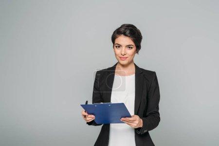attrayant mixte femme d'affaires tenant presse-papiers et regardant la caméra isolée sur gris