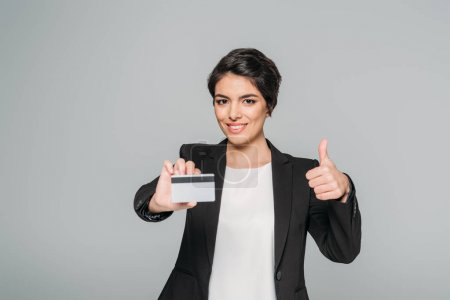 Photo for Smiling mixed race businesswoman holding credit card and showing thumb up isolated on grey - Royalty Free Image
