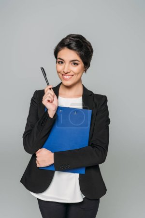 Photo for Cheerful mixed race businesswoman smiling at camera while holding clipboard and pen isolated on grey - Royalty Free Image