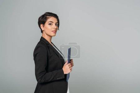 Photo pour Belle femme d'affaires de course mixte retenant le presse-papiers et regardant la caméra d'isolement sur le gris - image libre de droit