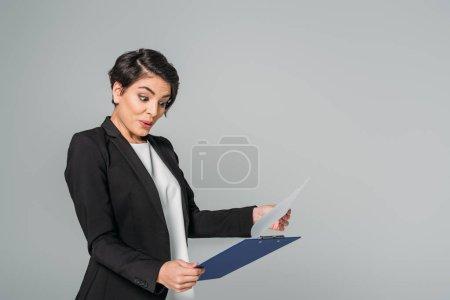 Foto de Sorprendido empresaria de raza mixta mirando el portapapeles y gesturing aislado en gris - Imagen libre de derechos