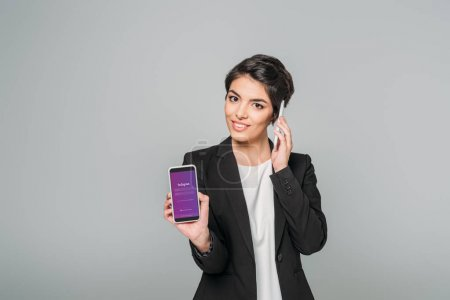 Photo for KYIV, UKRAINE - APRIL 24, 2019: Pretty mixed race businesswoman talking on smartphone and showing smartphone with Instagram app on screen isolated on grey. - Royalty Free Image
