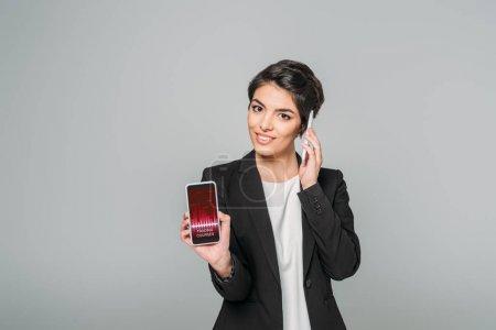 Photo pour Belle femme d'affaires de course mixte affichant le smartphone avec l'application de cours de négociation à l'écran tout en parlant sur le smartphone isolé sur le gris - image libre de droit