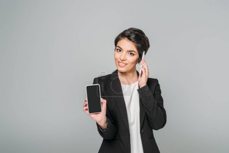 Photo for Young mixed race businesswoman talking on smartphone while holding smartphone with blank screen isolated on grey. - Royalty Free Image