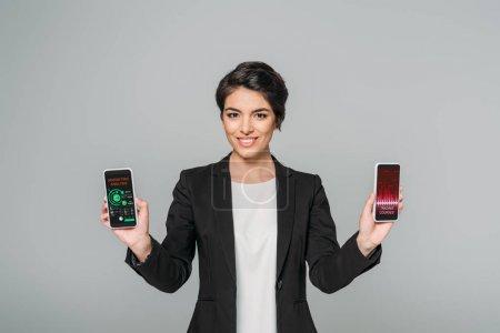 Photo pour Femme d'affaires mélangée souriante retenant des smartphones avec des cours de négociation et des apps d'analyse de marketing sur l'écran isolé sur le gris - image libre de droit