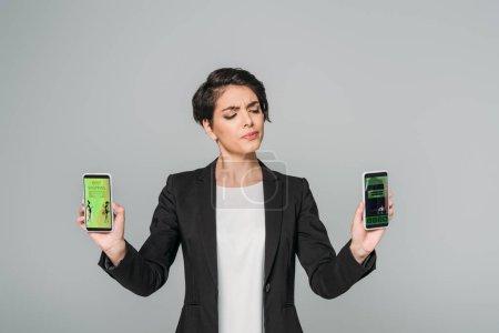 """Photo pour Jeune femme d'affaires métisse et sceptique tenant des smartphones avec les meilleurs achats et réservant des applications à l """"écran isolée sur gris - image libre de droit"""