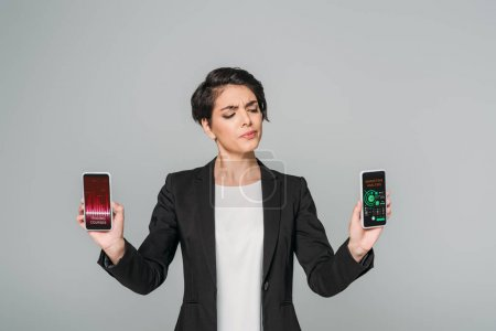 attractive mixed race skeptical businesswoman holding smartphones with trading courses and marketing analyses apps on screen isolated on grey