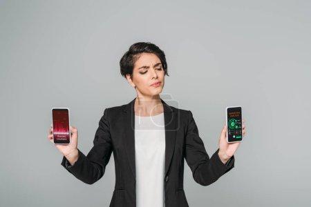 Photo pour Attractive race mixte sceptique femme d'affaires tenant des smartphones avec des cours de négociation et des analyses de marketing applications à l'écran isolé sur le gris - image libre de droit