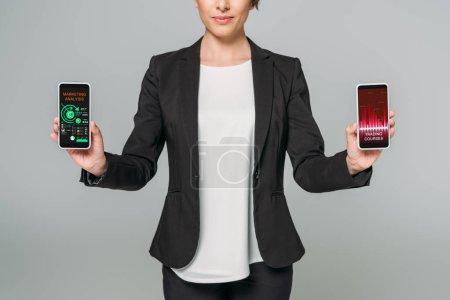 Photo pour Vue partielle de femme d'affaires de course mélangée retenant des smartphones avec des cours de négociation et des apps d'analyse de marketing sur l'écran isolé sur le gris - image libre de droit