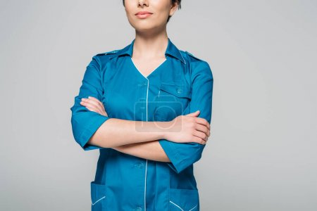 Photo for Cropped view of young mixed race nurse posing at camera with crossed arms isolated on grey - Royalty Free Image