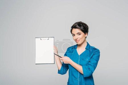 Photo pour Médecin de course assez mixte pointant vers du papier blanc sur un presse-papiers isolé sur le gris - image libre de droit