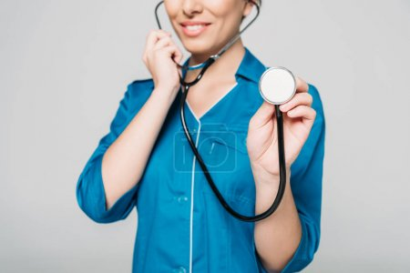 Photo for Partial view of young mixed race nurse in uniform using stethoscope isolated on grey - Royalty Free Image
