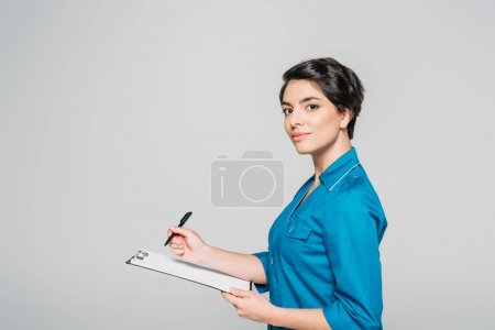 Photo for Attractive nurse in uniform writing ob clipboard and looking at camera isolated on grey - Royalty Free Image