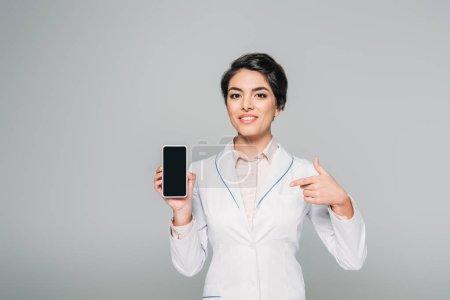 Photo pour Docteur mélangé gai de course pointant avec le doigt au smartphone avec l'écran blanc isolé sur le gris - image libre de droit