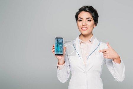 Photo pour Docteur mélangé de course de sourire pointant avec le doigt au smartphone avec l'essai d'ADN sur l'écran isolé sur le gris - image libre de droit