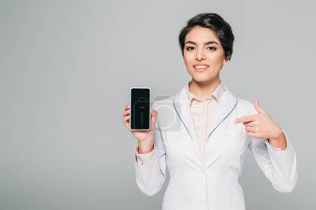 Photo for Cheerful mixed race doctor showing smartphone with blank screen isolated on grey - Royalty Free Image