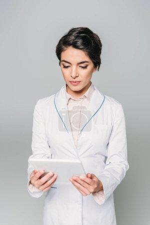 Photo pour Médecin de race mixte attentif dans le manteau blanc utilisant la tablette numérique d'isolement sur le gris - image libre de droit