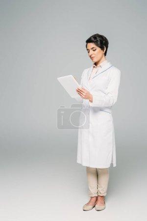 Photo pour Beau docteur mélangé de course dans le manteau blanc utilisant la tablette numérique sur le fond gris - image libre de droit