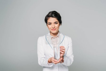 Photo for Pretty mixed race doctor holding glass of water while looking at camera isolated on grey - Royalty Free Image