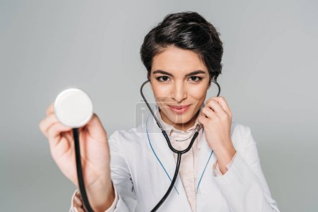 selective focus of cheerful mixed race doctor using stethoscope isolated on grey