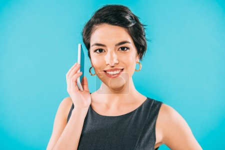 Photo for Cheerful mixed race woman talking on smartphone while smiling a camera isolated on blue - Royalty Free Image