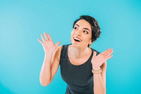 Photo pour Femme mélangée excitée de course faisant des gestes tout en regardant loin isolé sur le bleu - image libre de droit