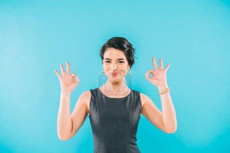Photo pour Joyeuse femme mixte montrant un geste correct tout en souriant à la caméra isolée sur bleu - image libre de droit