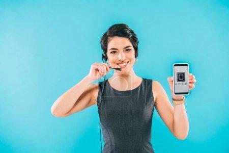 Foto de KYIV, UKRAINE - APRIL 24, 2019: Smiling mixed race call center operator showing smartphone with Uber app on screen isolated on blue. - Imagen libre de derechos