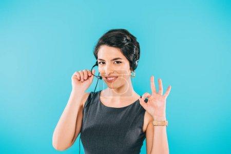 Foto de Operador de centro de llamadas de carrera bastante mezclado en auriculares que muestran signo ok mientras mira la cámara aislada en azul - Imagen libre de derechos