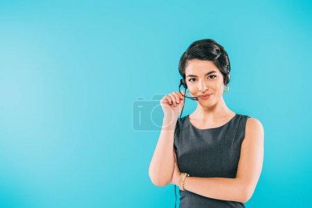 Foto de Beautiful mixed race call center operator in headset looking at camera isolated on blue - Imagen libre de derechos