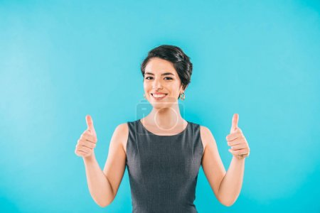 cheerful mixed race woman showing thumbs up and smiling at camera isolated on blue