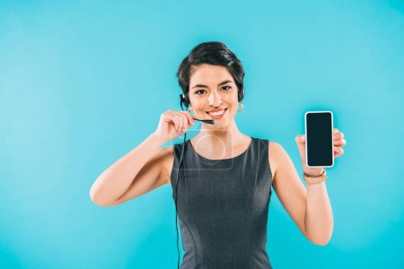 Foto de Smiling mixed race call center operator in headset showing smartphone with blank screen isolated on blue - Imagen libre de derechos