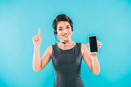 Foto de Attractive mixed race call center operator showing idea sign and holding smartphone with blank screen isolated on blue - Imagen libre de derechos