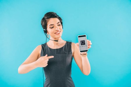 Foto de KYIV, UKRAINE - APRIL 24, 2019: Attractive mixed race call center operator presenting smartphone with Uber app on screen isolated on blue. - Imagen libre de derechos