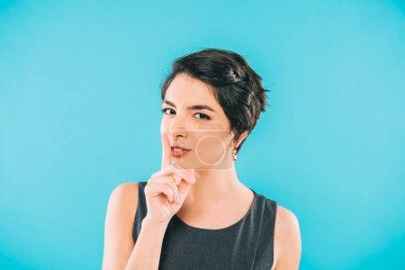 Photo pour Attrayant mixte femme montrant geste de silence et de regarder la caméra isolée sur bleu - image libre de droit