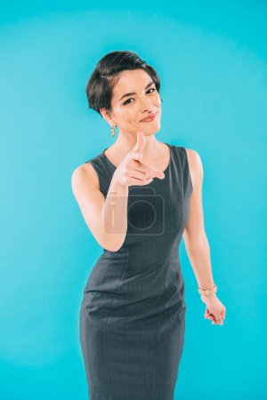 Photo for Cheerful mixed race woman smiling and pointing with finger at camera isolated on blue - Royalty Free Image