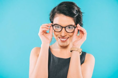 Photo for Attractive mixed race businesswoman in glasses smiling at camera isolated on blue - Royalty Free Image