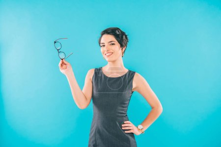 Photo for Cheerful mixed race businesswoman holding glasses while posing at camera with hand on hip isolated on blue - Royalty Free Image